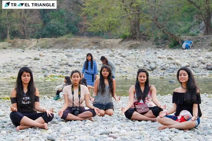 A group of girls posing in the meditation pose by the banks of the Kosi river in Jim Corbett