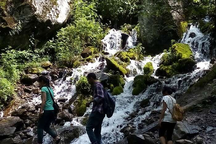Travelers walking past the waterfall in Tosh