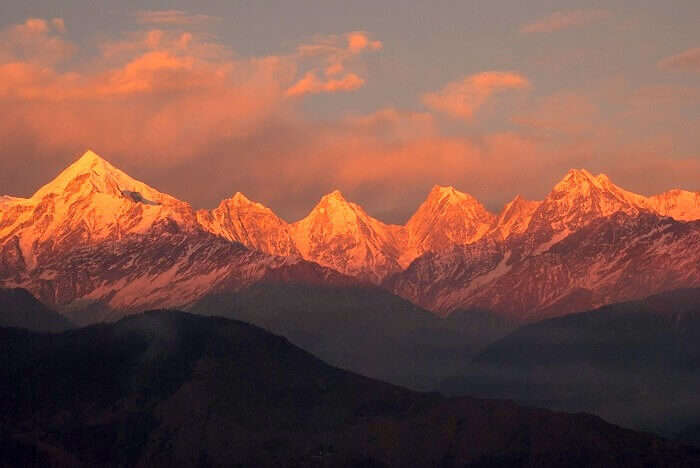 A sunset view of the reddish-orange color over the snow capped Himalayas as seen from Kausani