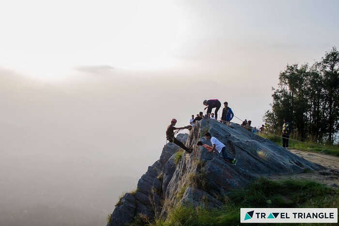 A bunch of travelers trying rock climbing on one of the weekend trips from Delhi to Mukteshwar