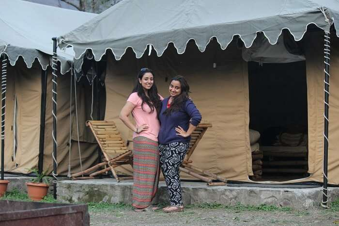 Girls pose for a photograph outside the tents in Rishikesh