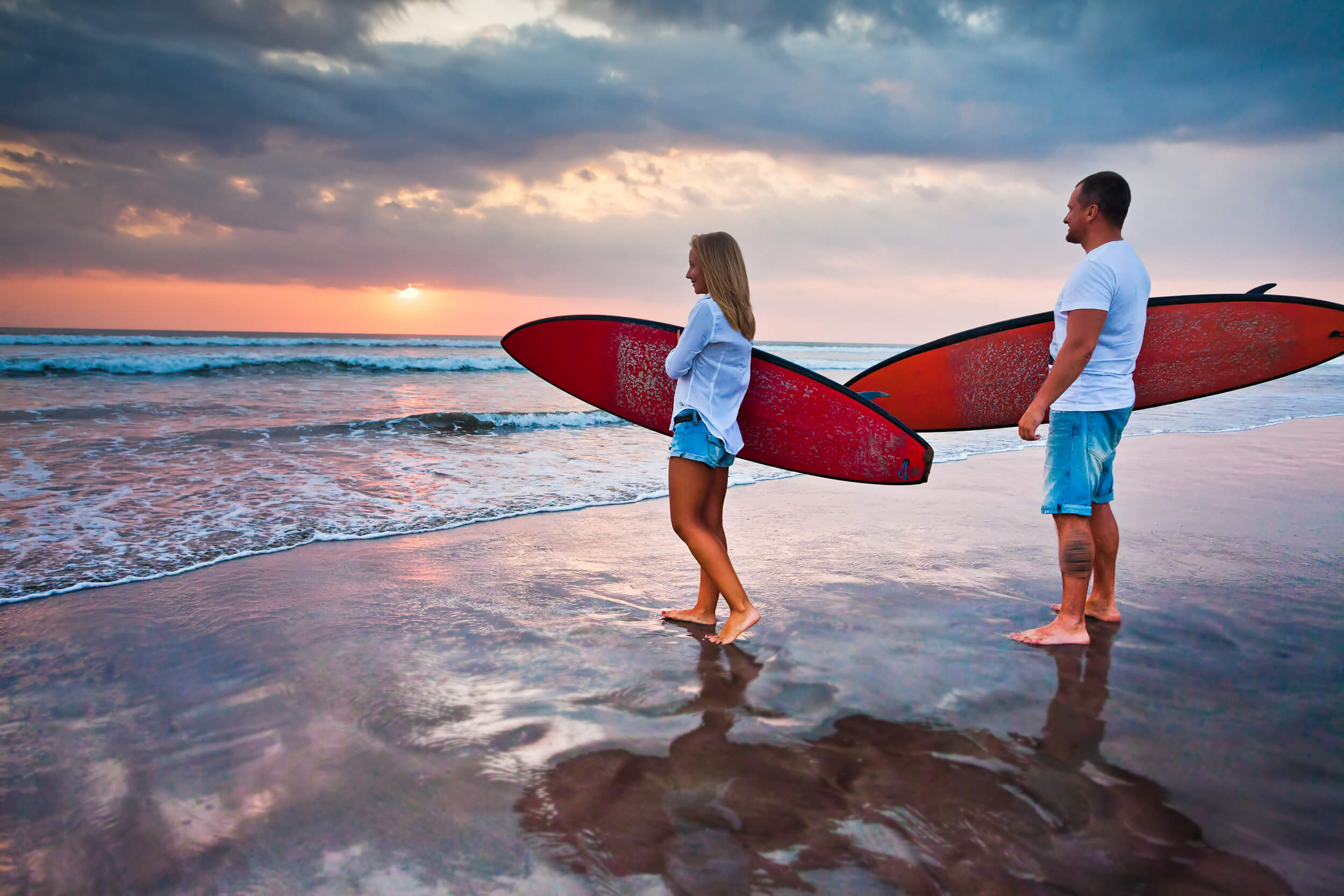 a couple holding surfing board on a beach