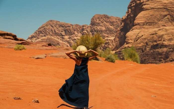 women wearing long western dress with hat in the deserts of Wadi Rum