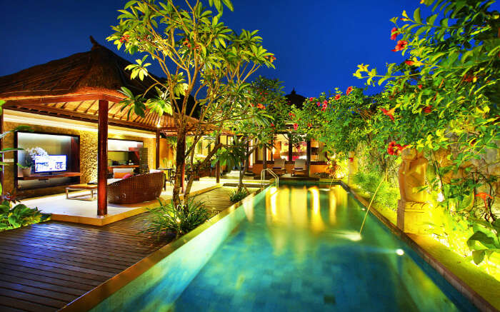 A beautiful outdoor pool in a resort at night