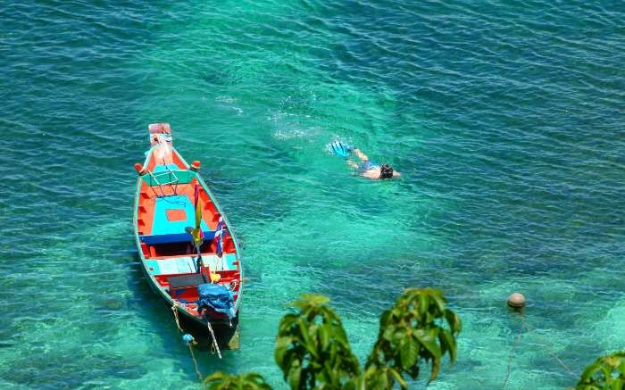 A guy swimming beside a colourful boat in blue waters