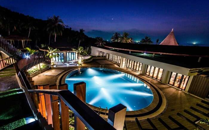 An outdoor pool in a hotel glowing at night