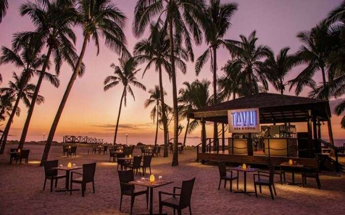 Bar and grill setup of a resort on a private beach surrounded by palm trees