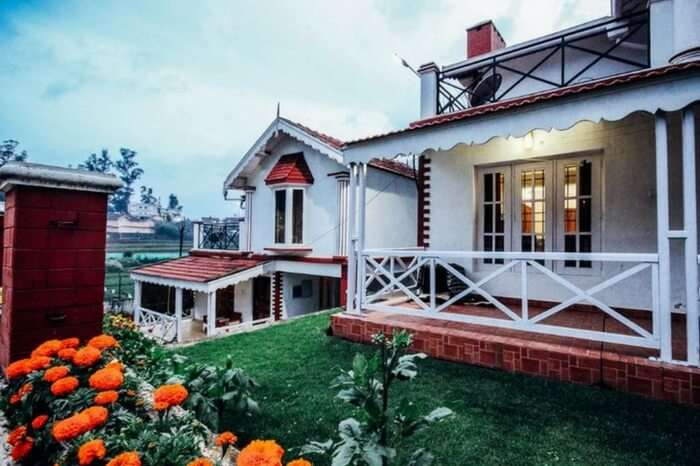 Balcony with garden view of one of the villas of Pine View Stay in Ooty