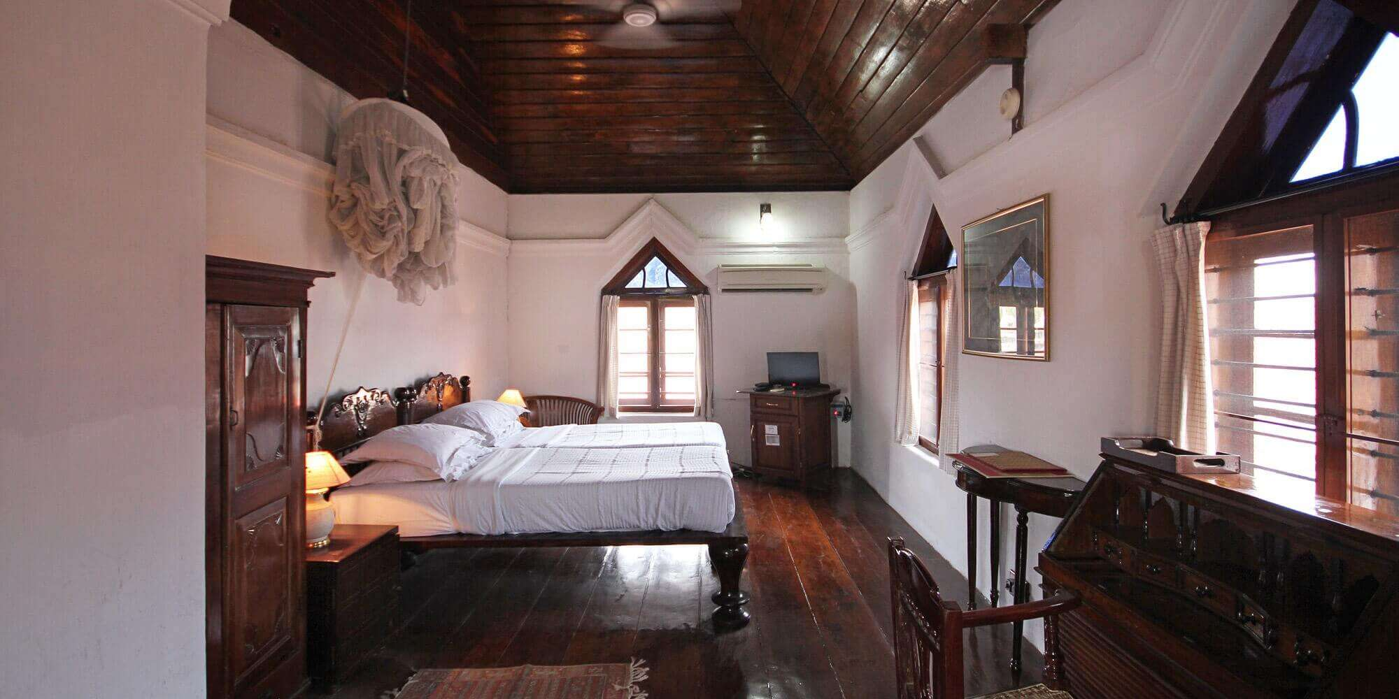 an old style hotel room in Kerala with a bed inside