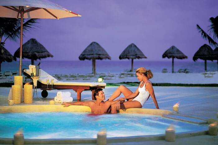 A couple on a honeymoon in Mexico relaxing in the swimming pool at Secrets Capri Riviera Cancun