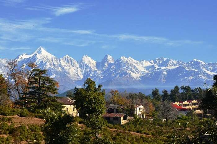 A view of the snow-capped hills in the backdrop of the cottages in Chaukori in Uttarakhand
