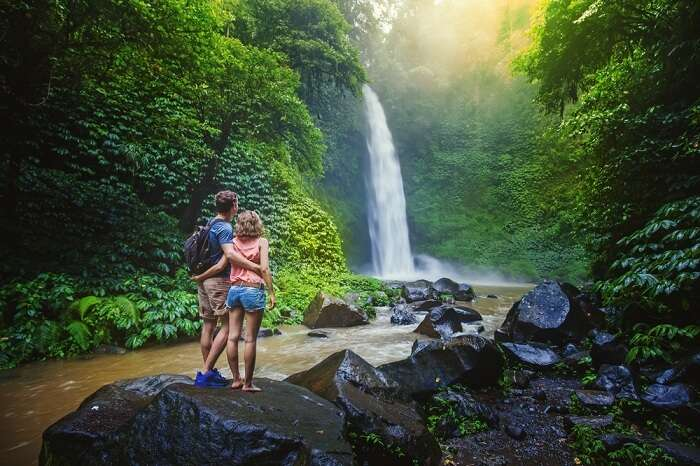 A couple looking at the gorgeous waterfall in the rainforests of Malaysia