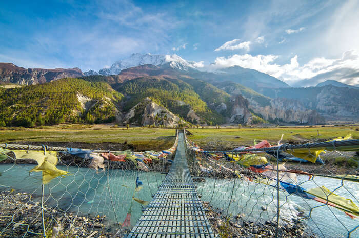 prayer flags tied to a bridge in the hills of Annapurna