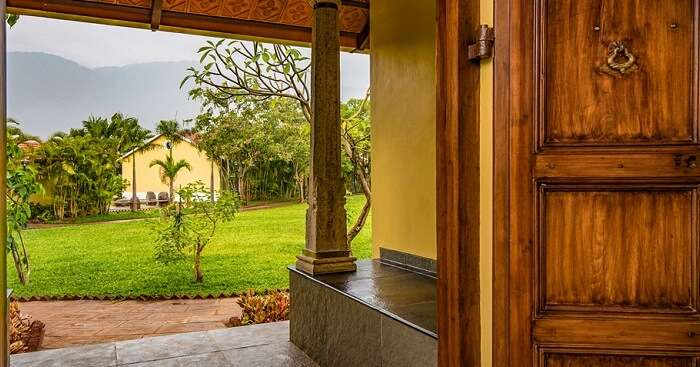 A shot of the lawn and cottages from inside another cottage at Dvara Siruvani Resort in Coimbatore