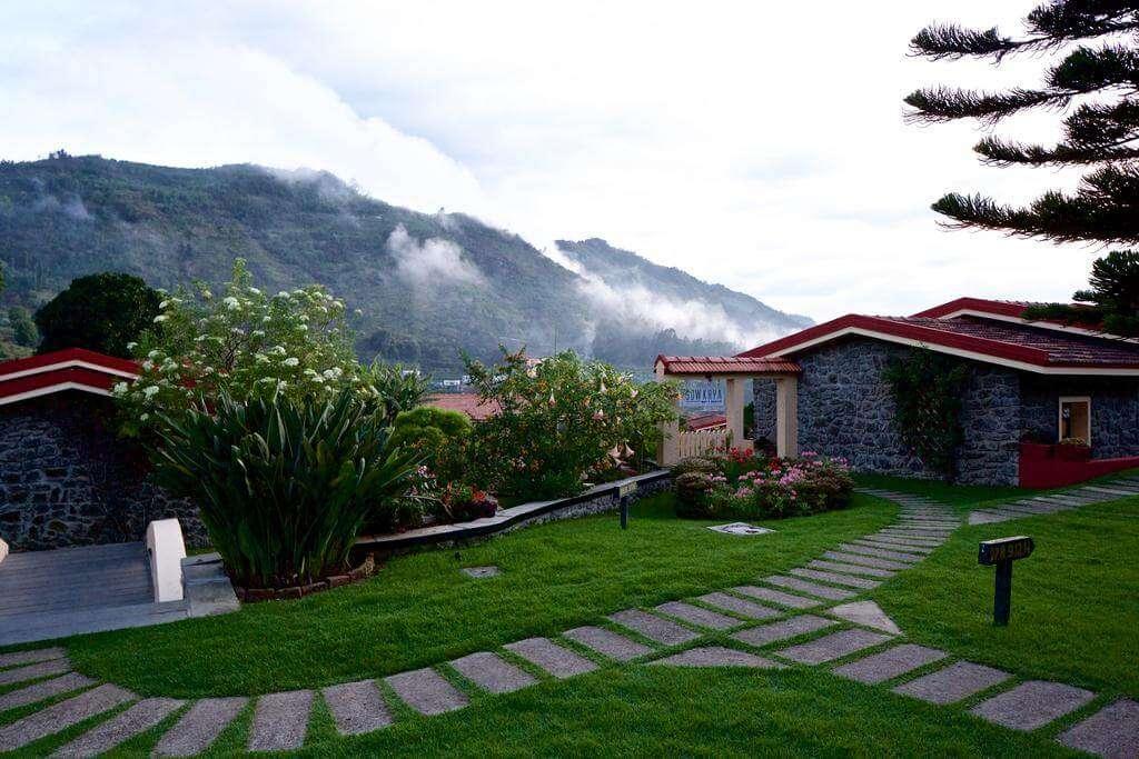 a green paved lawn of a resort in Kodaikanal hills