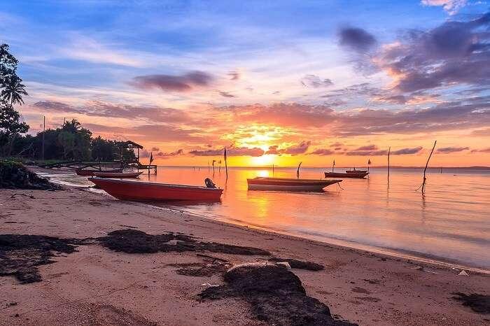 enjoy a riveting sunset at nelayan beach