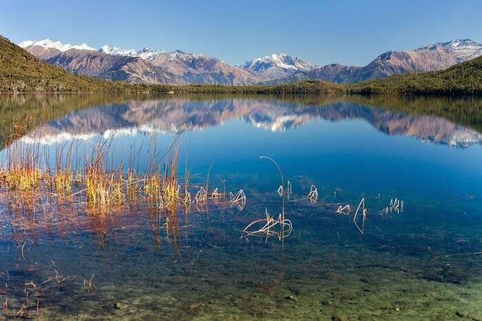 a reflection of snowclad mountains on Rara Lake