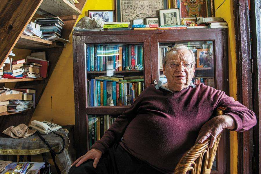 Ruskin bond sitting in his room filled with books