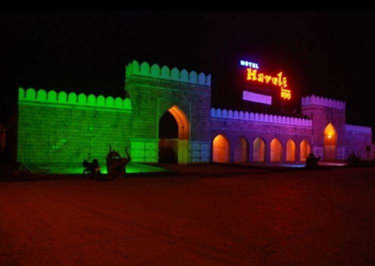 a haveli style entrance of a resort painted with colourful lights