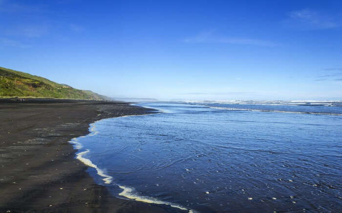 The black sand by the Kariotahi Beach in Auckland