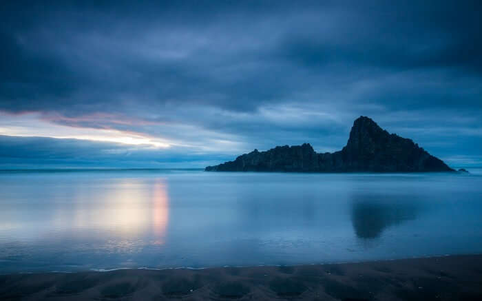 The quiet waters at Karekare Beach in Auckland at sunset