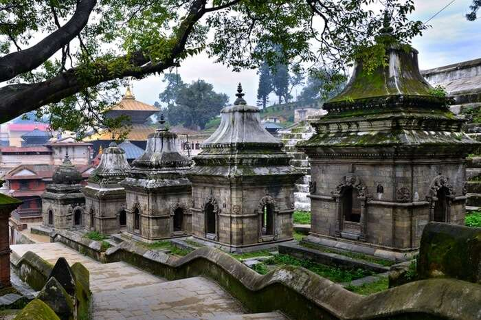 A row of moss covered small ancient temples in a temple premises