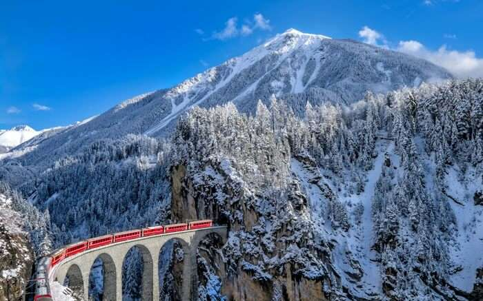 The Glacier Express coming out of a tunnel in the Swiss Alps in Switzerland