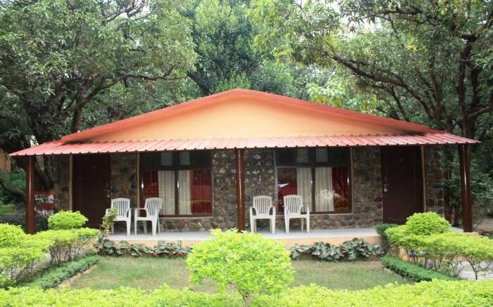 hut like hotel with four plastic chair in the garden
