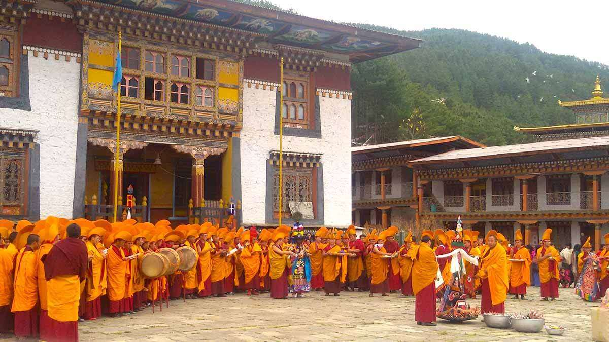 monks wearing orange robs in a monastery in Bhutan