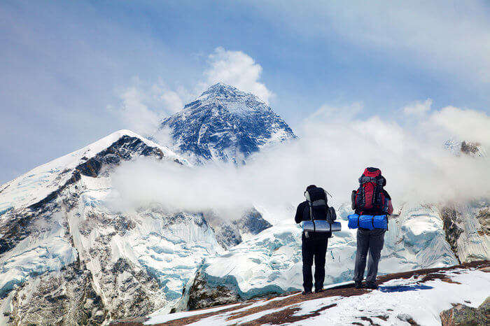 two climbers looking at the snow laden mountains