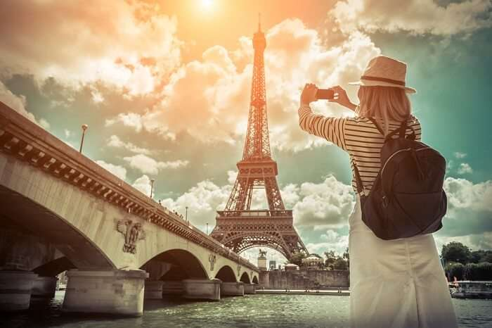Woman tourist taking a selfie near the Eiffel tower in Paris under sunlight and blue sky