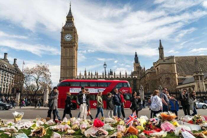 A bus passing by the Big Ben Tower on the Westminster Bridge in London