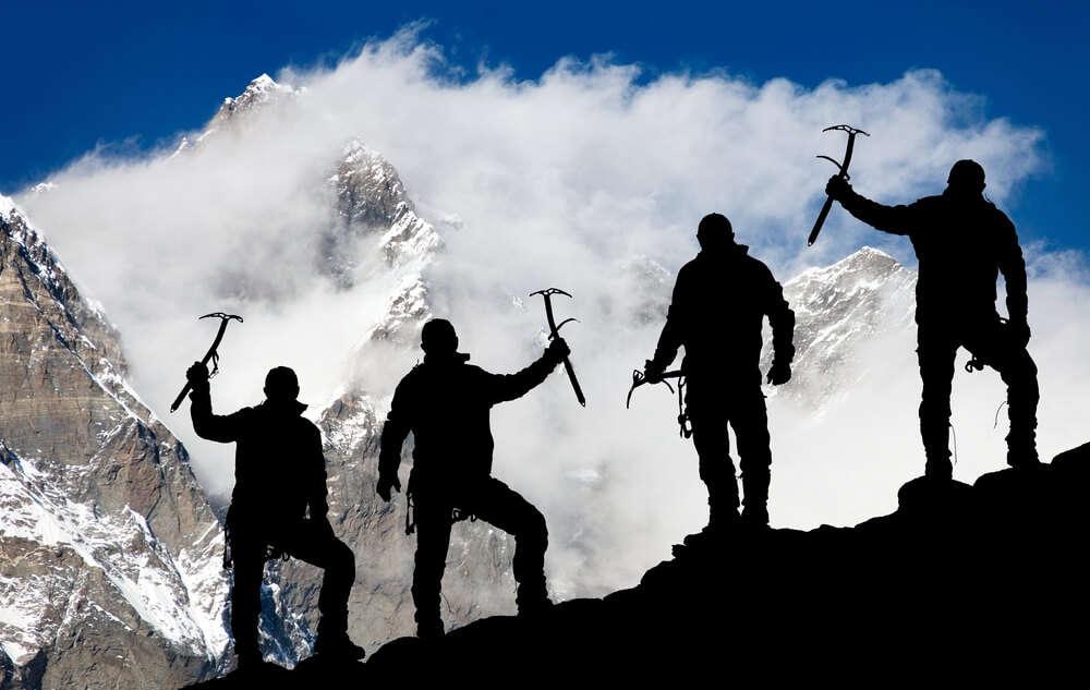 three men holding trekking equipment