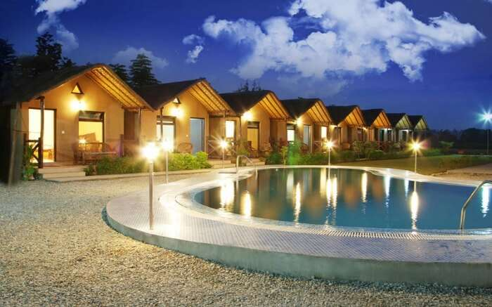 wooden style well lit resort with a small swimming pool