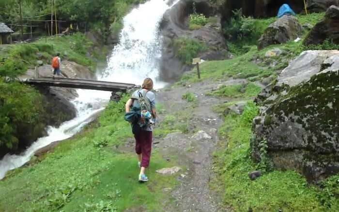 A traveler walking past the stream in Tosh in Himachal