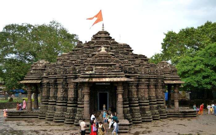 An ancient temple with an orange flag on top of