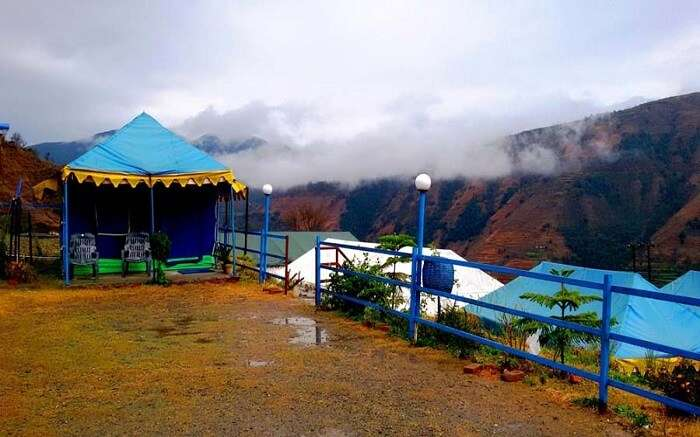 Blue colour tent in a ground in misty mountains