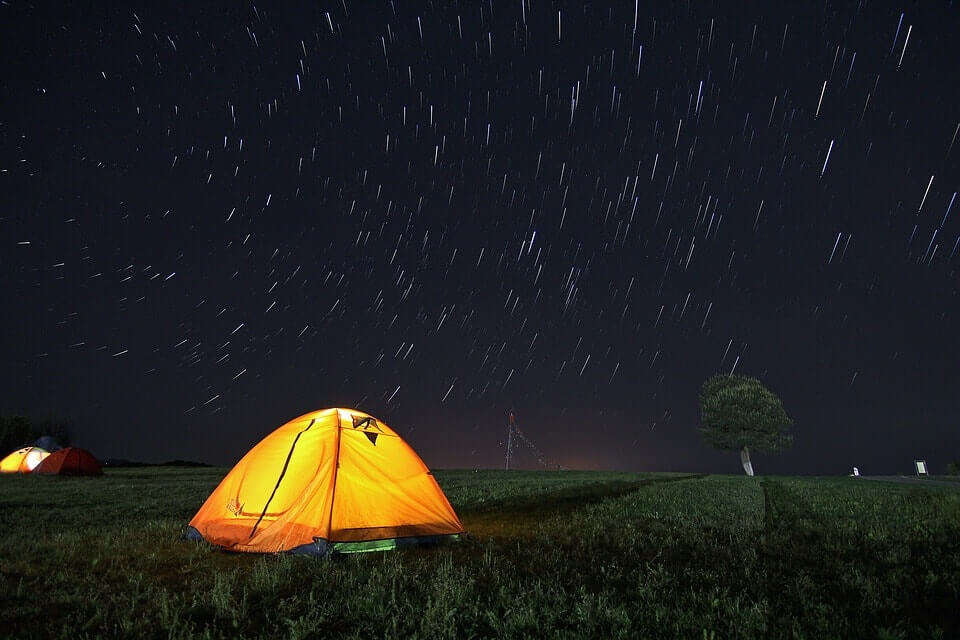 a well lit yellow camp at night in mountains