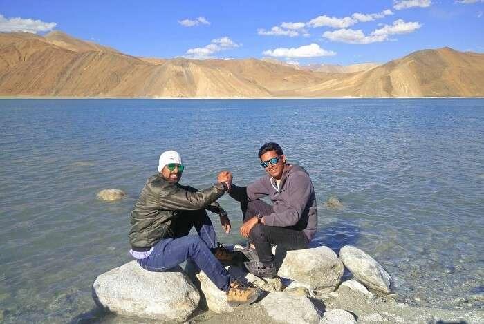 ninad and friend sitting near pangong lake