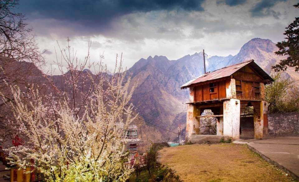 an old house on the side of a road in mountains