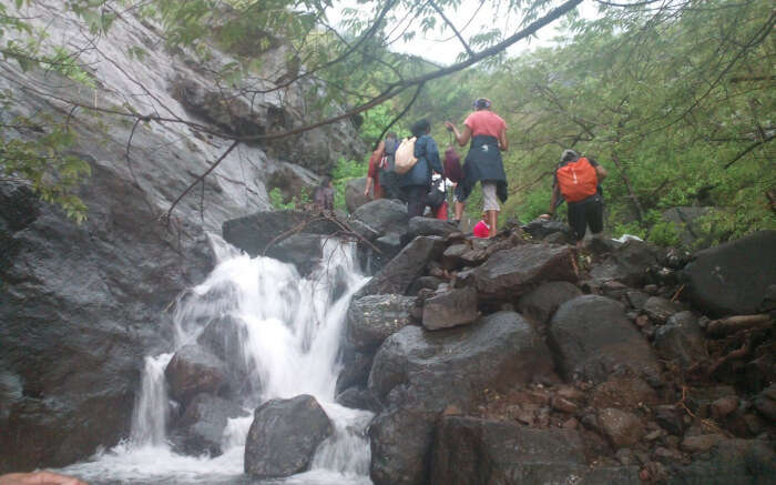 People trekking through a small waterfall