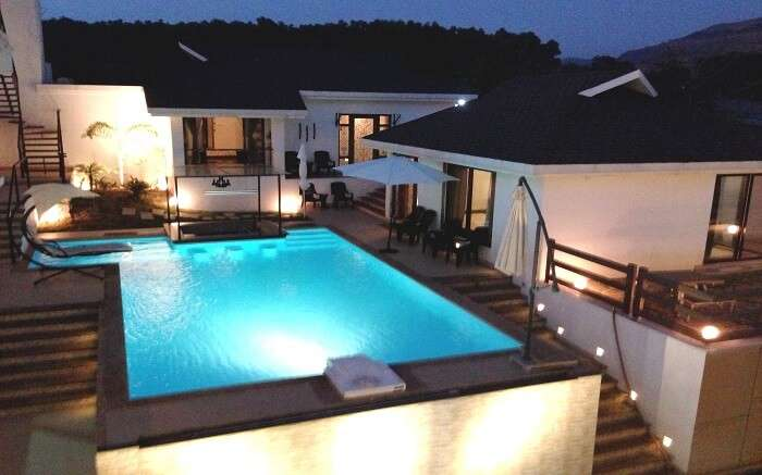 The well lit pool of Casa Dios Luxury Villas in Lonavala