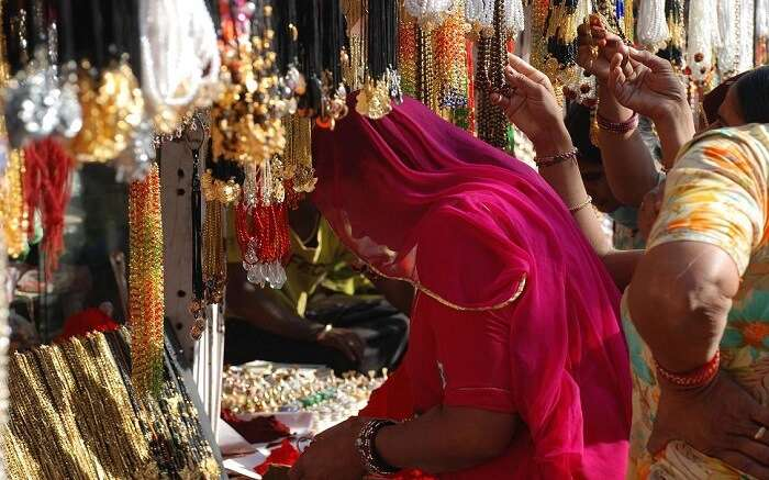 Women buying jewelry from shops in pushkar