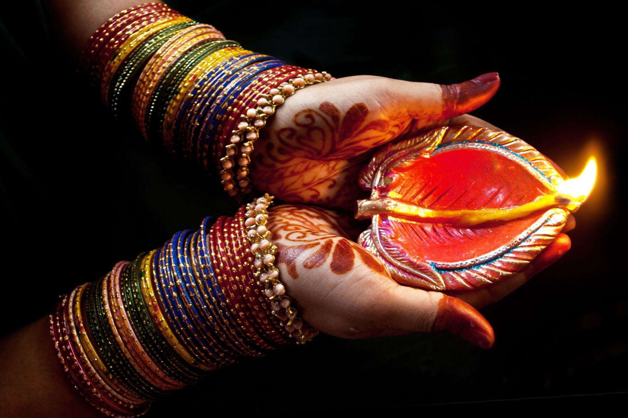 a women wearing bangles carrying a diya in her hands
