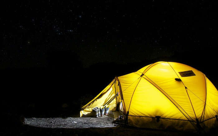 a yellow colour well lit tent pitched under a dark sky