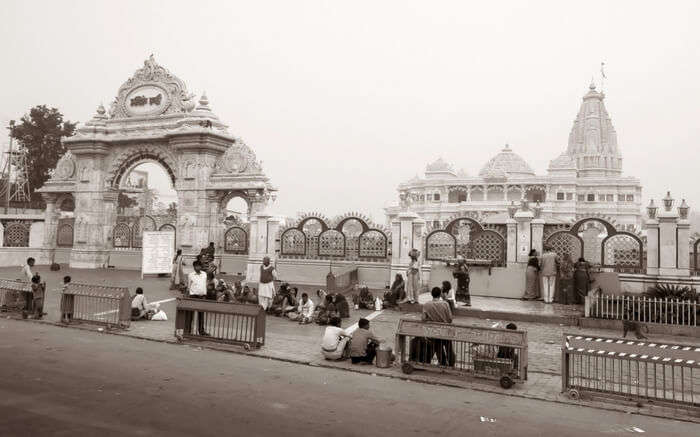 People sitting outside an ancient temple in Vrindavan near Agra