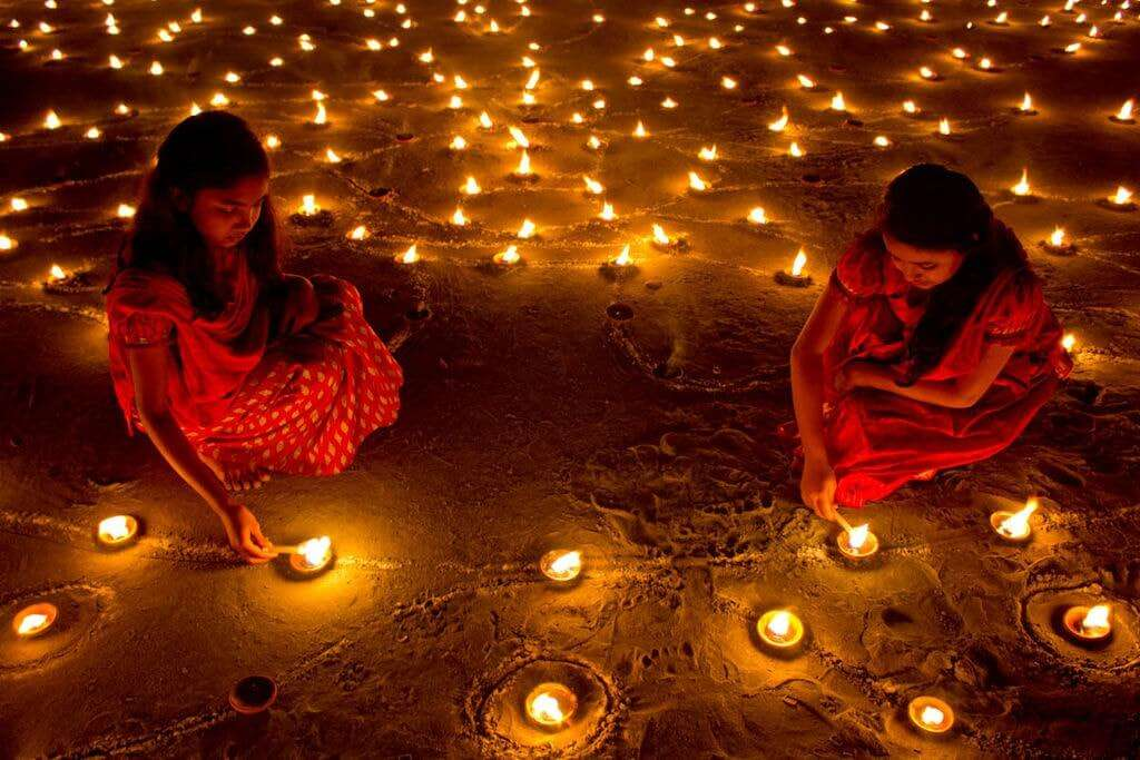two little girls lightening diyas