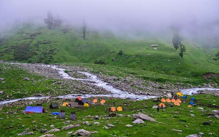 A beautiful campsite covered in mist at Hampta Pass