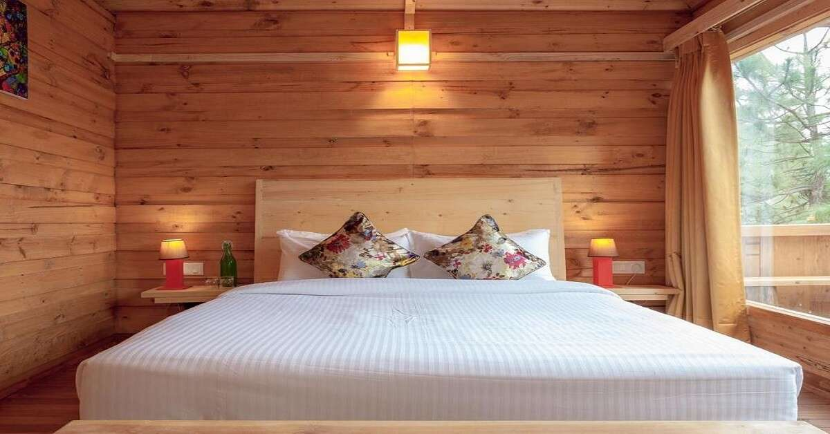 A beautiful wooden resort room with a white bed and glass window
