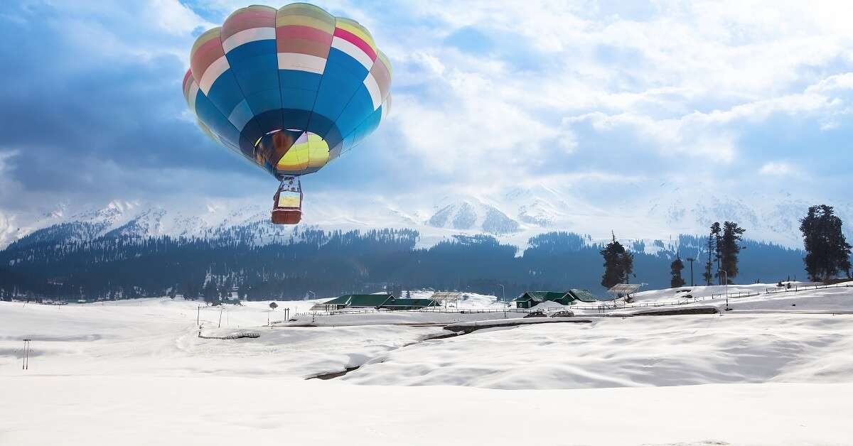 A hot air balloon flying over a village in Gulmarg in Kashmir
